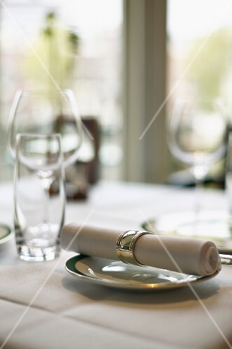 A fabric napkin on a plate and empty glasses on a table in a restaurant