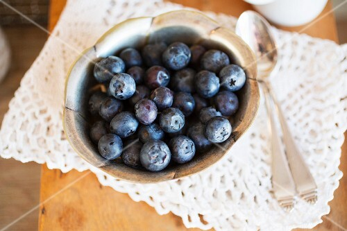 A bowl of fresh blueberries on a crocheted doily
