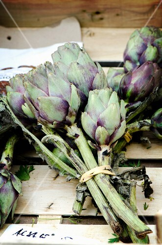 A bunch of artichokes in a wooden crate