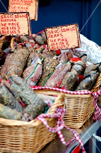Various types of salami on market stand