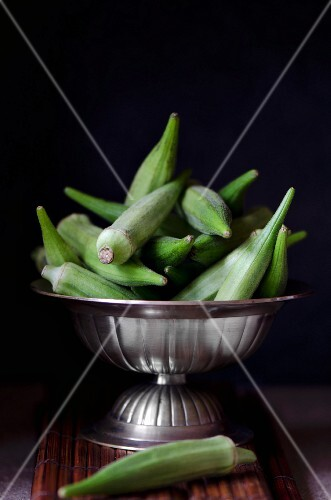 Fresh okra pods in a silver bowl