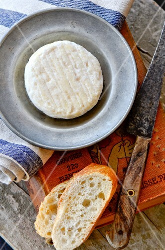 St. Marcellin cheese on a pewter plate with baguette