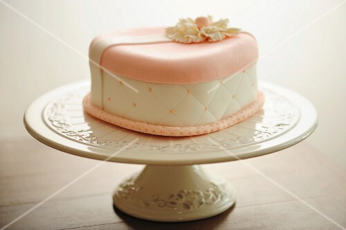 A festive pink and white marzipan cake on a cake stand