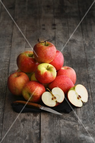 A stack of apples on a dark wooden surface