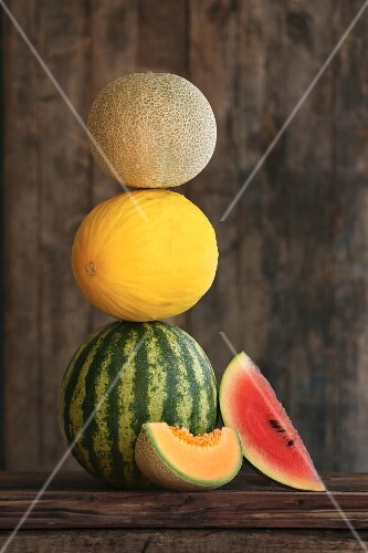 A stack of various melons, rustic wooden board, whole and sliced