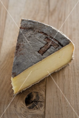A slice of cow's milk cheese on a wooden surface
