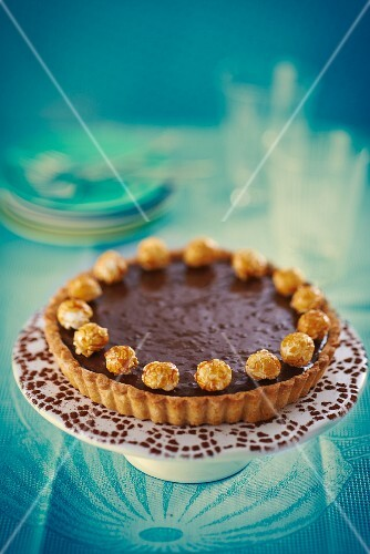 Chocolate tart with popcorn on a cake stand
