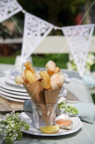 Chips and fried prawns in small paper bags