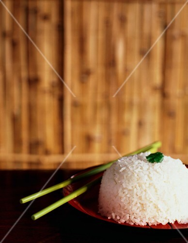 Steamed rice in a red bowl with green chopsticks