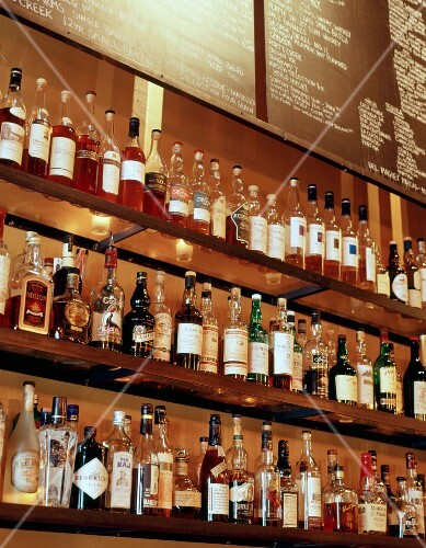 Bottles of spirits on a glass shelf behind a bar