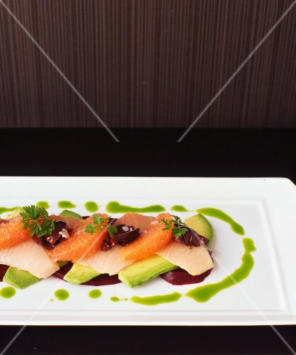 Wahoo sashimi on a bed of avocado and beetroot with grapefruit and olive fillets served with parsley sauce