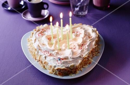 A heart-shaped cake with burning candles for birthday
