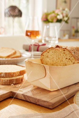 Home-made bread in a poplar wood baking mould on a chopping board