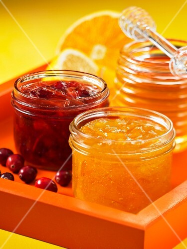 A jar of cranberry and orange marmalade and a jar of honey and lemon marmalade