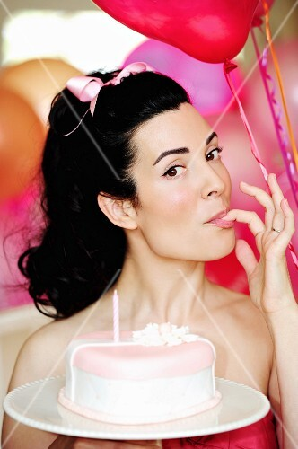 A dark haired woman holding a marzipan cake with a candle on a cake stand
