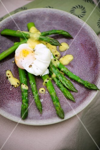 A poached egg on green asparagus with a mustard vinaigrette