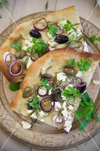 Pita bread topped with olives, rosemary, onions and sheep'S cheese