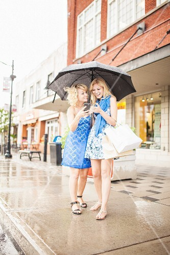 To laughing sisters looking at a smartphone under a grey umbrella
