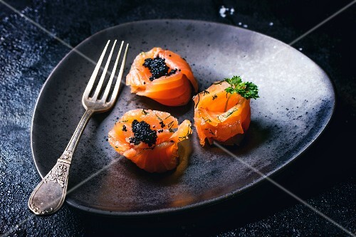 Salmon rolls with black caviar on a plate with a fork