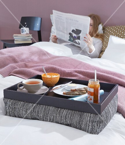 Breakfast in bed on a homemade padded tray and a woman in the background reading a newspaper