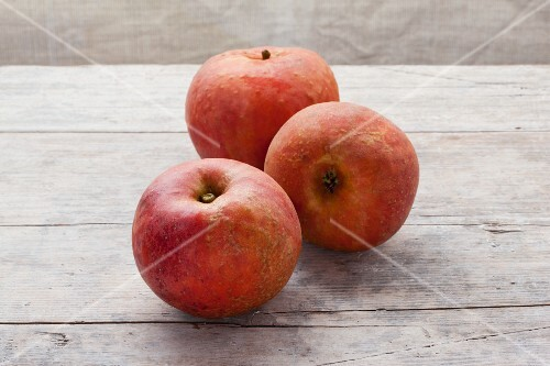 Three organic Red Boskop apples on a wooden surface