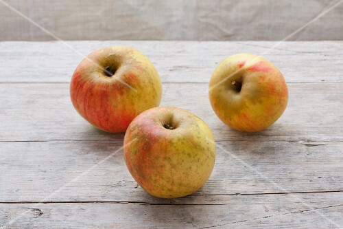 Three organic Kaiser Wilhelm apples on a wooden surface