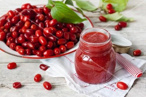 Fresh cornelian cherries and a jar of jam