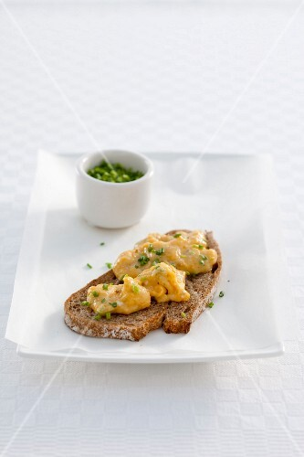 A slice of bread topped with scrambled eggs and chives