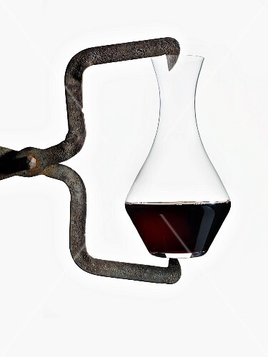 A carafe of red wine being held by and iron tool