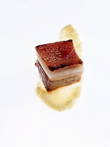 A piece of honey-glazed pork belly with vegetable purity