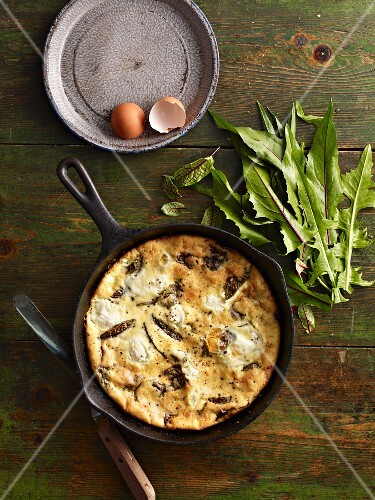 Ricotta frittata with sorrel in a pan on a wooden table