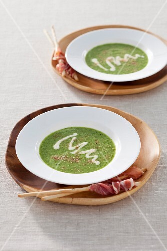 Lettuce soup with dried mushrooms served with grissini and bacon
