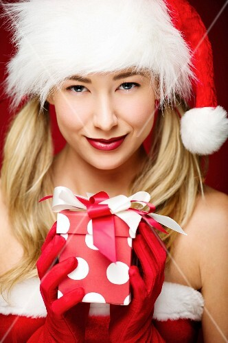 A young woman wearing a Father Christmas hat holding a present