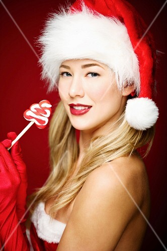 A young woman wearing a Father Christmas hat holding a lolly