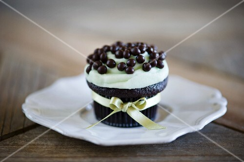 A chocolate cupcake decorated with chocolate drops