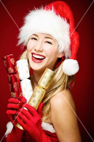 The young woman wearing Father Christmas hat holding crackers