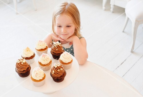A little girl sitting in front of creamy cupcakes