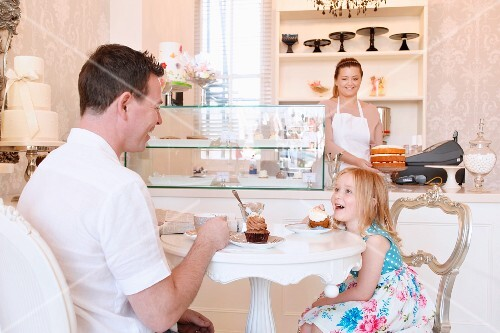 A blonde girl and her father in a cafe with large cupcakes