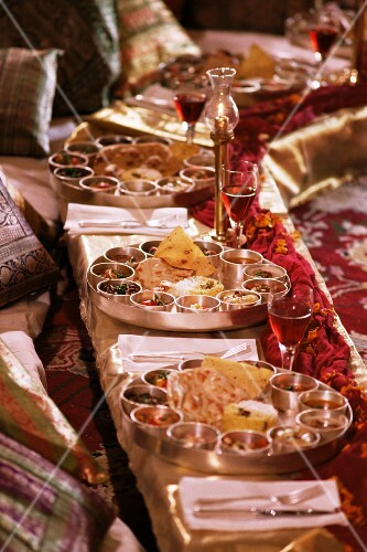 Traditional Rajasthani food served in brass bowls in the Grand Durbar Hall, Samode Palace, Samode, Rajasthan state, India