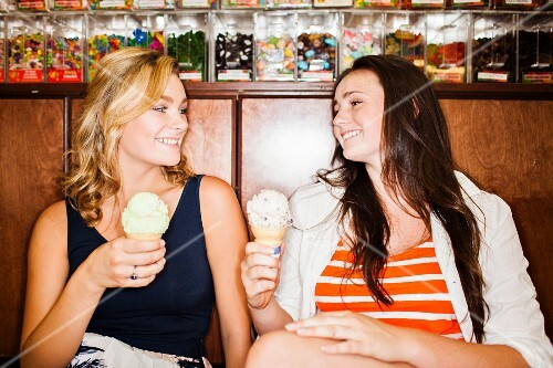 Two teenage girls eating ice cream in a cafe