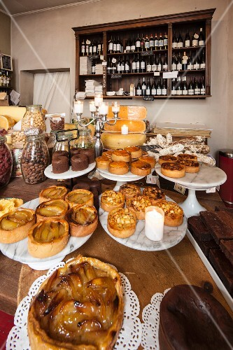 Various tarts, cheeses and wine in a delicatessen