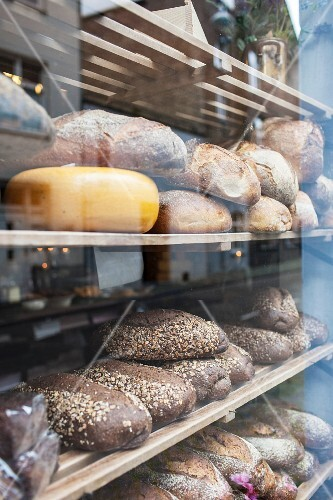 A wheel of cheese and various types of bread in the window of a bakery (close-up)