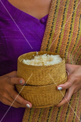 A woman holding sticky rice in bamboo baskets (Vientiane, Laos)