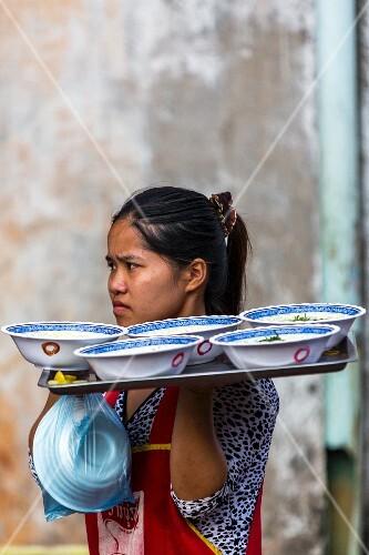 A waitress serving bowls of noodle soup (Vientiane, Laos)