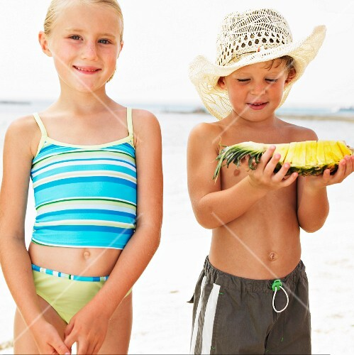 A boy and a girl on a beach with a slice of pineapple