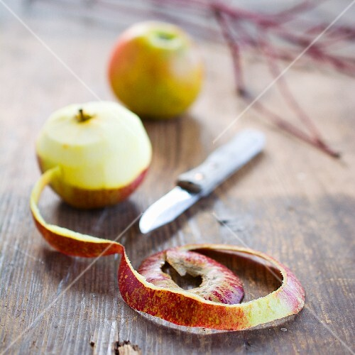 Apples, one partially peeled, on a wooden table