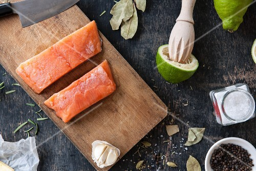 An arrangement of salmon fillets, garlic, limes and spices