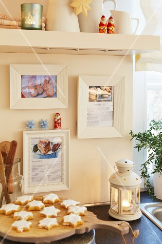A Christmassy kitchen scene with cinnamon stars and favourite recipes framed on the wall