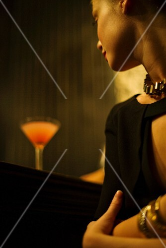 A woman sitting at a bar with a cocktail