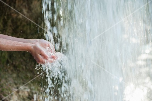 A person holding their hands under a waterfall